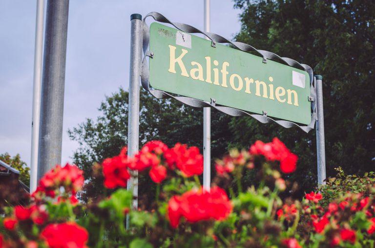 Ortseingangsschild in grün mit Blumen von Kalifornien (Schönberg, Schleswig-Holstein)