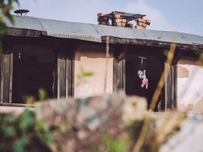 Marionettenpuppe im Fenster eines verlassenen Hauses in Pissen (Rodden, Sachsen-Anhalt)