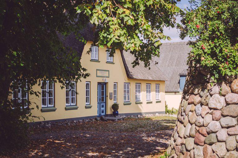 Gelbes Haus in Schweden (Mohrkirch, Schleswig-Holstein) im Schatten von Bäumen