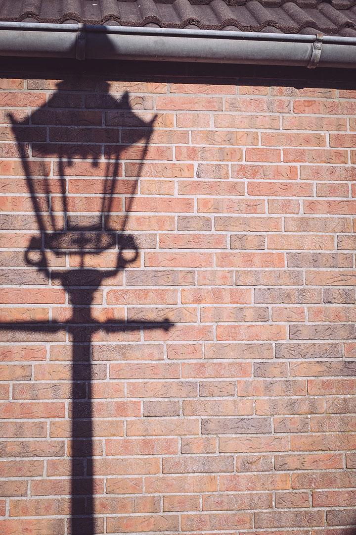 Schatten einer Laterne auf einer Mauer in Neustadtgödens (Sande, Niedersachsen)